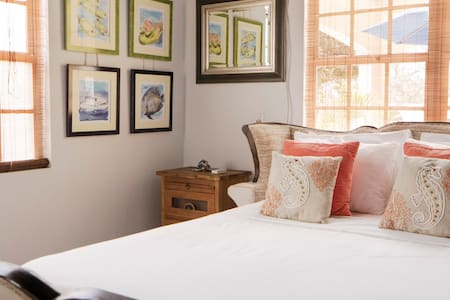 Sleigh bed and local art of Bonaire marine life brings tranquility to the bedroom.