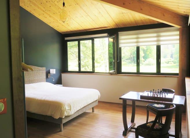 riante slaapkamer met hoog plafond en aan 2 zijdes ramen