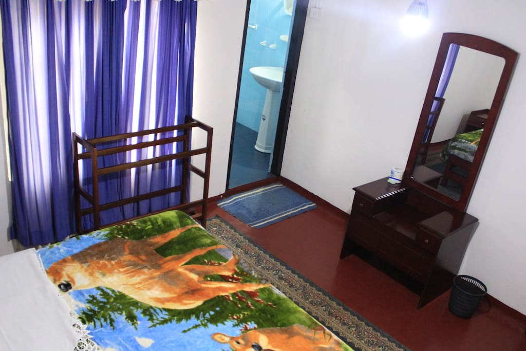 Room No. 2 with one triple bed with a private tiled bathroom with hot water shower.