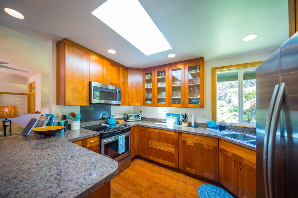 Spacious deluxe kitchen with skylight and large windows for enjoying the rainforest views while cooking.