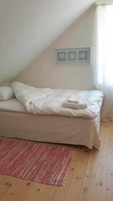 Sengen er redd opp med nystrøket sengetøy, dyne og pute med moskusdun fra Høie, et bade- og håndhåndkle.