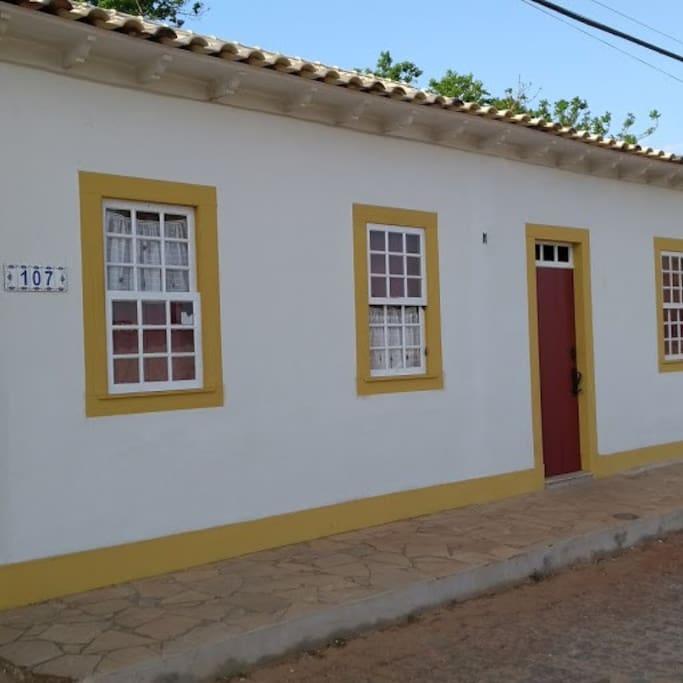 Nova fachada da casinha, com janelas de madeira, quihotinas e telhado