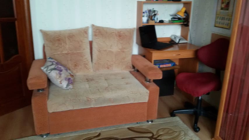 Выдвижной диван в зале, компьютерный стол и ноутбук. Зал