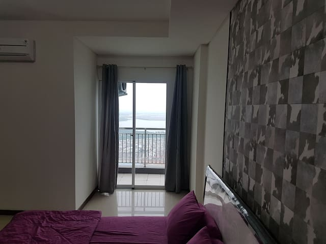 master bedroom with sea and city view on window balcony