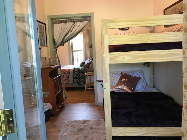 Comfy bunk beds with comfy chair and plenty of hooks for clothes , modern clip lamps over each bed for reading amd plenty of outlets for charging devices - bookcase with kids and adult reading materials