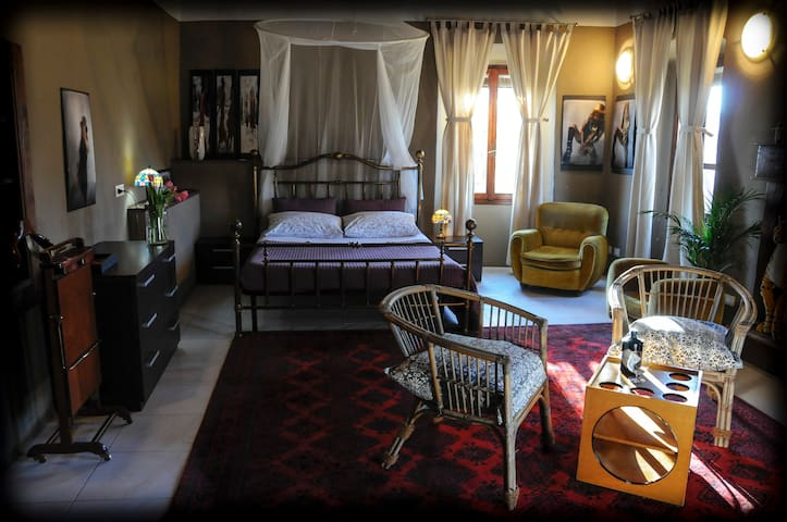 grande camera da letto con un letto  matrimoniale , poltrone , un letto singolo, molto luminosa con tre finestre.large bedroom with a double bed, armchairs, a single bed, very bright with three windows