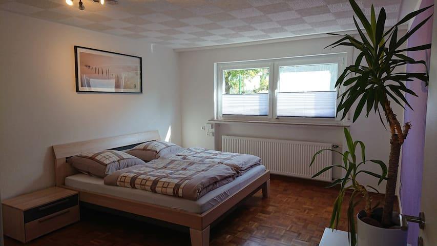 Schlafzimmer mit großem Fenster.  Rollo zum verdunkeln und Fliegengitter auf einer Seite zum Lüften.