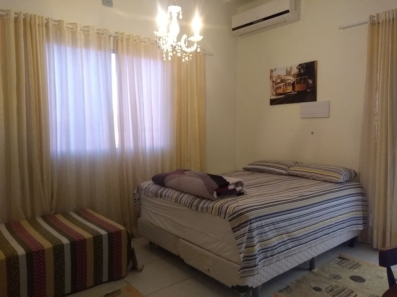 Cama box Queen confortável, ar condicionado split, decoração com quadros de vários países europeus.