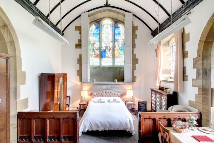 The bedroom area of the studio apartment, with our beautiful William Morris stained glass window