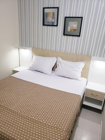 Suite com cama tamanho Queen. Aparadores laterais com iluminação. Belíssima decoração.