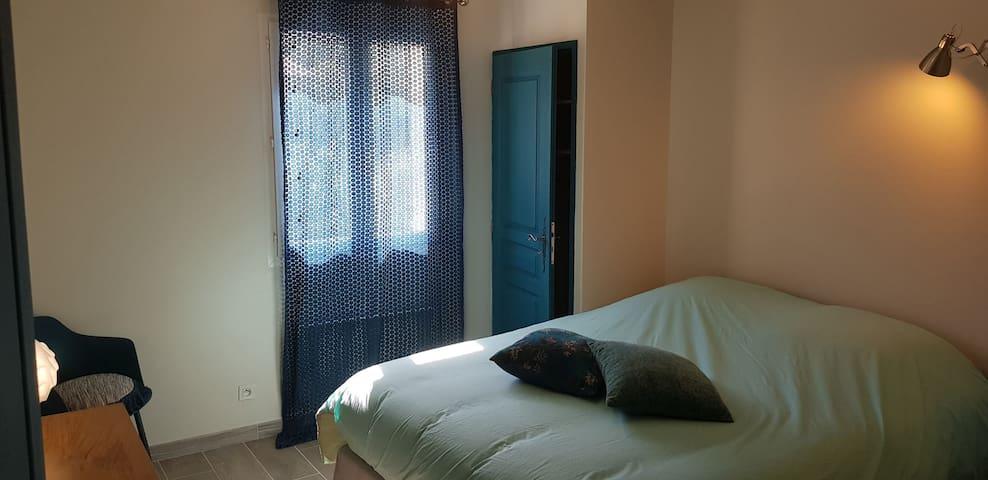 """Chambre spacieuse avec son lit """"queen size"""" grand confort et placard de rangement derrière la porte."""