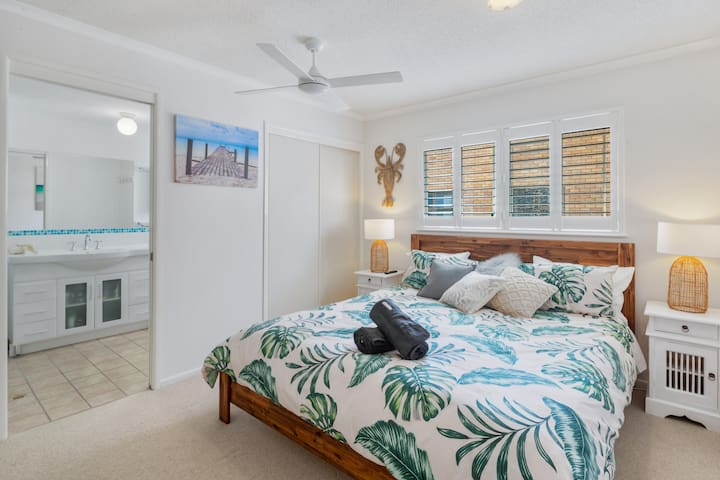 The apartment's master bedroom features a king size bed, ensuite, built in cupboard, Netflix enabled TV, ceiling fan and screened window