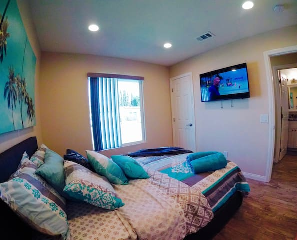 Second bedroom with full size bed and extra storage space underneath. There is also a mounted television and a closet with hangers provided for your convenience.  A window with bright natural sunlight helps give this room a comfortable feel!
