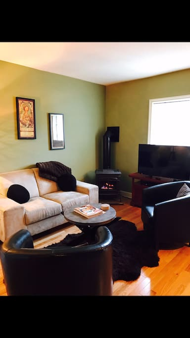 """Living room with cozy fur rug, 43"""" smartTV, warm gas fireplace, local zines."""