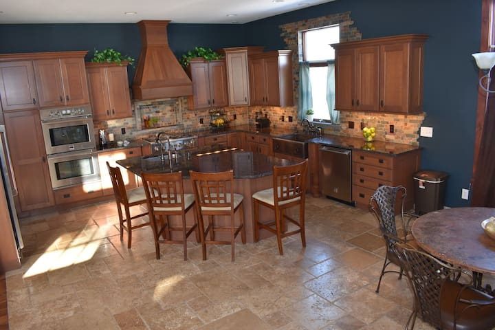 Large kitchen with ample rock edge granite countertops, dbl ovens ,gas cooktop ,2 sinks including hand hammered copper sink below window
