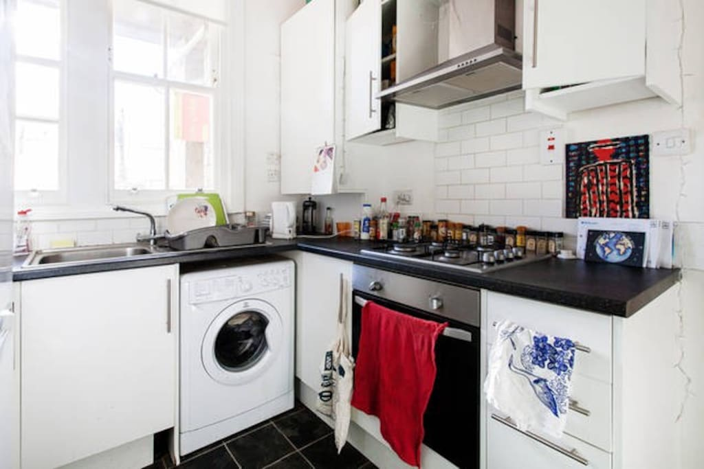 Shared kitchen with gas hob, washing machine and a fridge.