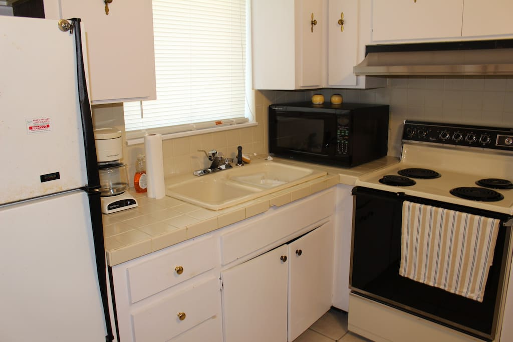 Full refrigerator, stove and microwave with dishes, silverware, pots and pans.