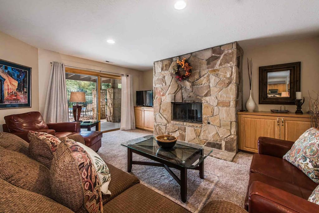 "Living room area with stone fireplace,42"" HDTV with cable television and free WiFi. Sliding doors with access to communal pool"