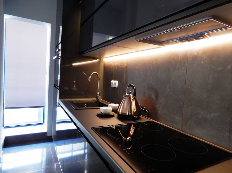 Modern kitchen fully equipped with necessary appliances and utensils