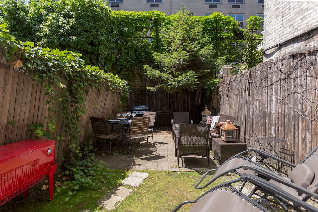 Private garden with BBQ, cooler, lounge chairs, seating and dining areas