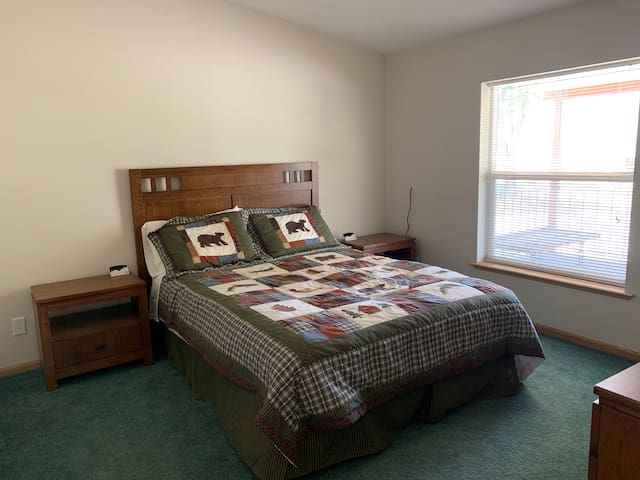 2nd bedroom has a queen bed set with 2 night stands, a 6 drawer dresser with mirror, and a closet with hangers.
