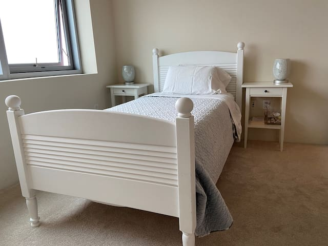 Twin bed in the second bedroom with firm mattress. Closet with custom drawers