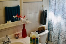 First bathroom with towels, soap, shampoo, condition and hand soap.