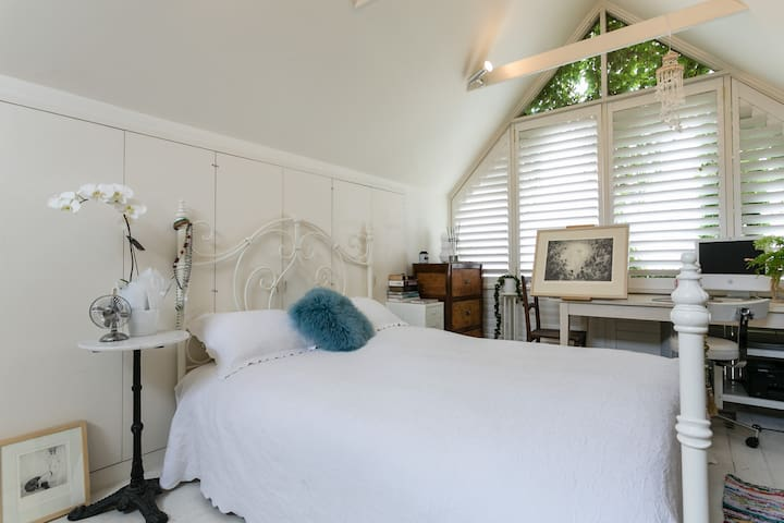 The loft is a light white room featuring a queen bed.