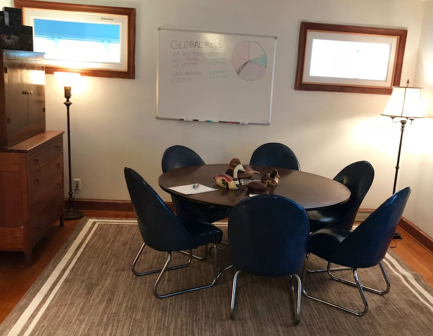 Living room conference table, six chairs and a mounted whiteboard are perfect for a business meeting — or a friendly game of cards.