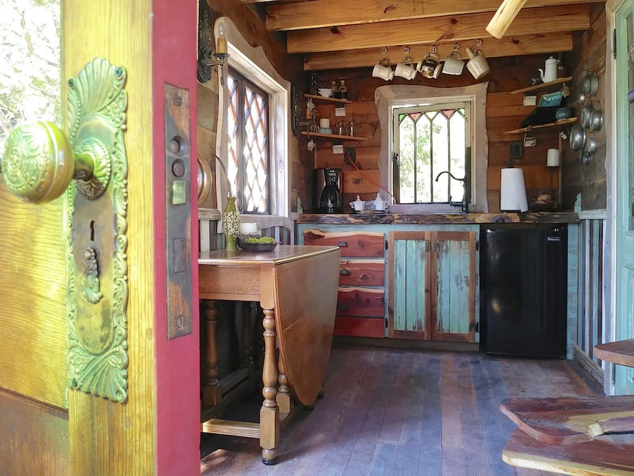 The kitchen includes a small fridge, a coffee maker, cutlery, utensils, dishes, goblets, and linens. A hot plate and pots and pans available by request.