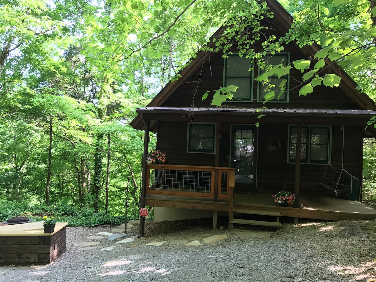 Cedar Bluff Cabin in the spring with fire pit area on the left