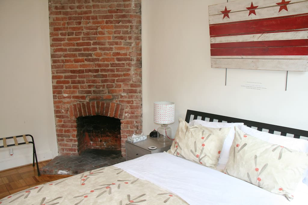 Front Bedroom: parquet wood floors, fireplace, and two windows.
