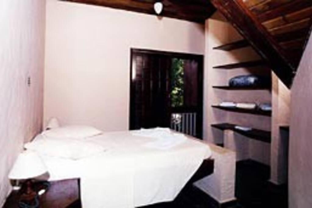 Quarto com cama de casal, banheiro e sacada para o fundo da casa