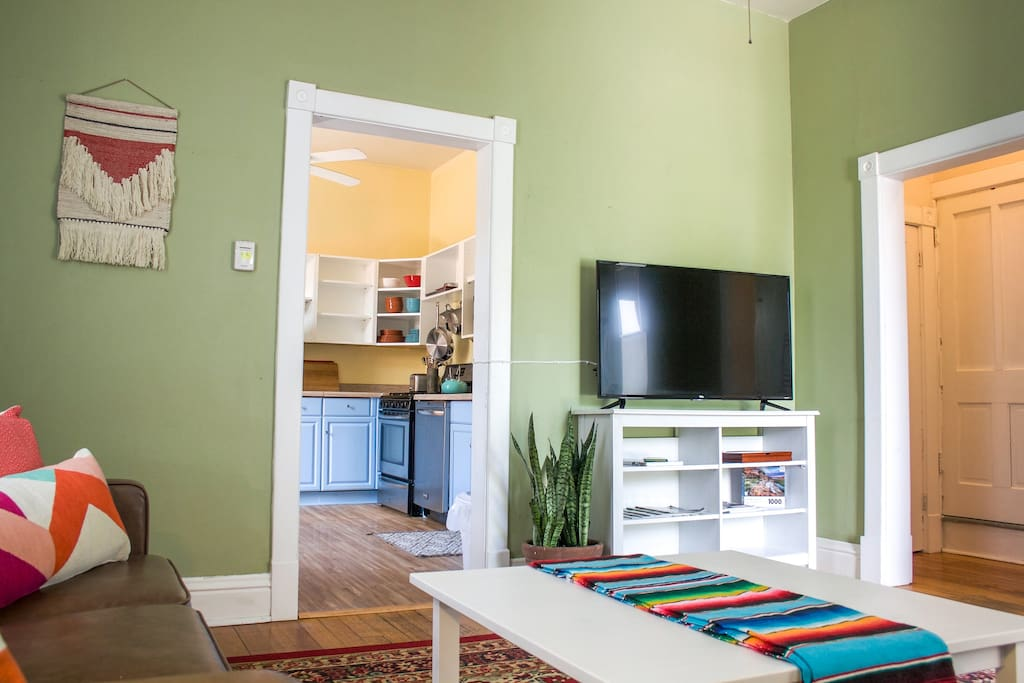 """Relax in the sunny and colorful living room with leather sofas and 42"""" television."""