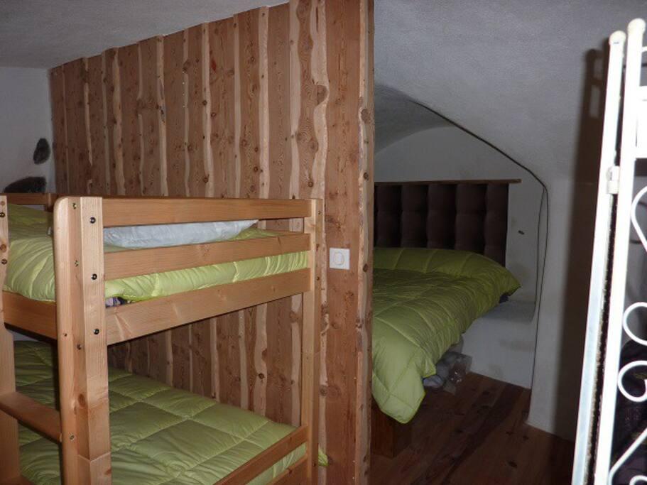 coin nuit : un grand lit 2 personnes et 2 lit superposés.