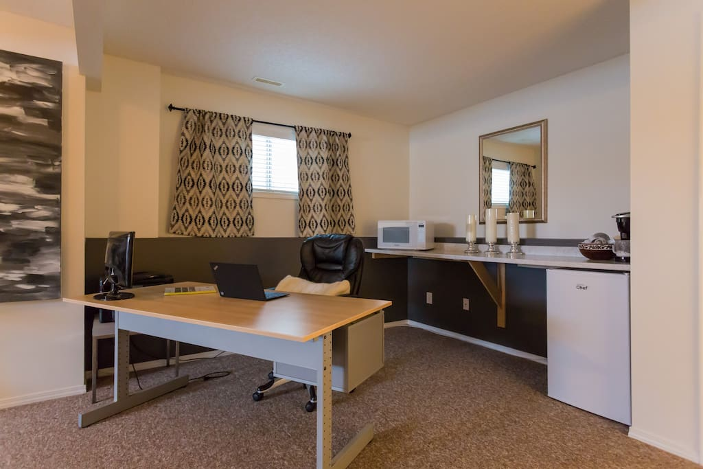 Here's your office and bistro area! Your own mini fridge, microwave and Keurig are ready for you. A large desk and chair looking out into the room makes for a cozy place to work from home.