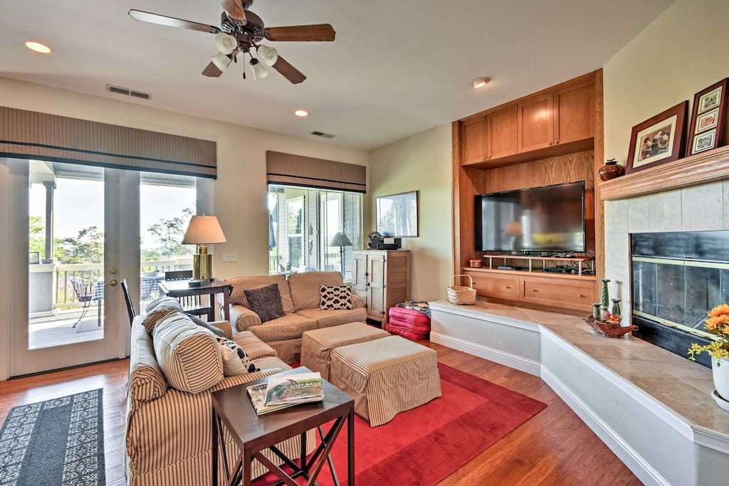 The living room is filled with natural light and features a wood-burning fireplace.