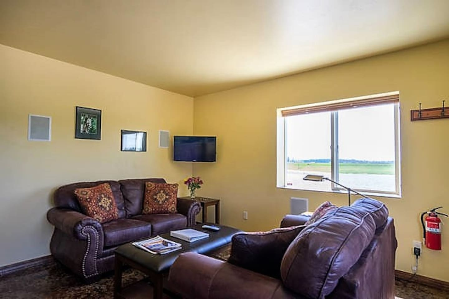 Comfortable living room with two love seats, a coffee table, two end tables, and a flat screen TV.