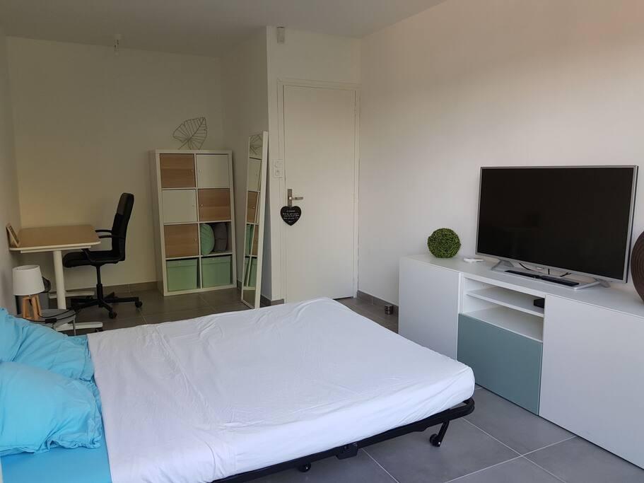 Grande chambre avec TV écran plat, bureau et rangements