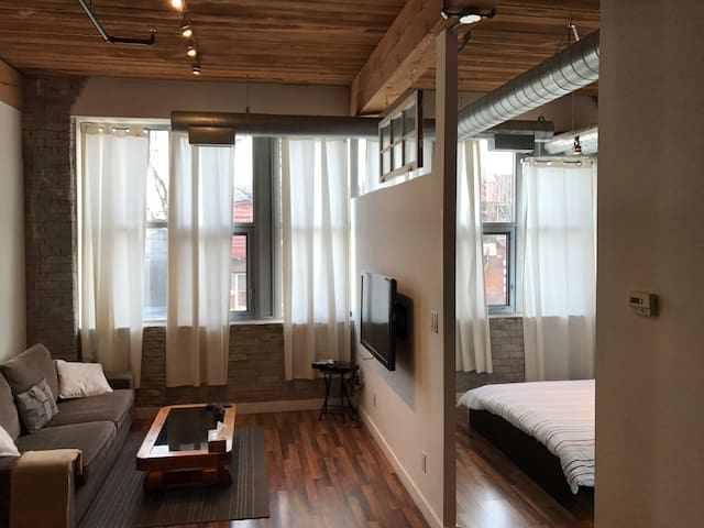 Open concept living room showcasing the vaulted wooden ceiling with exposed air ducts.