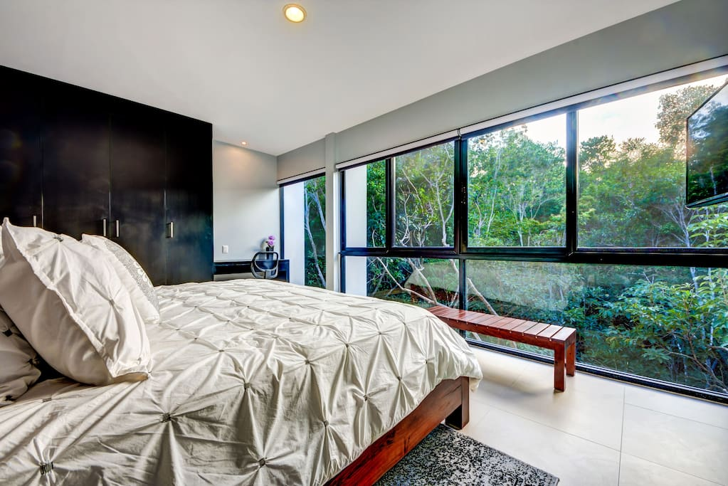 Main bedroom with large windows for an amazing jungle view
