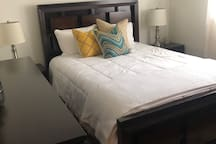 Queen Bed with down alternative comforter, cozy cotton quilt and an abundance of cozy pillows.  Step out of bed onto a soft plush rug covering cherry hardwood flooring.