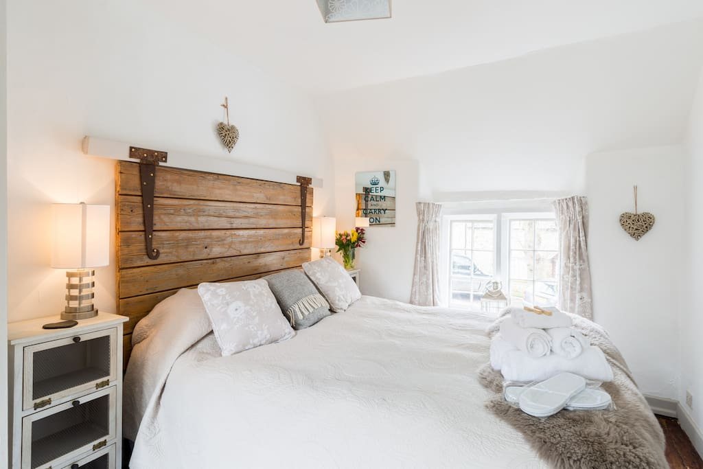 The Kingsize bedroom has rustic wooden floorboards, ample wardrobe space and sink