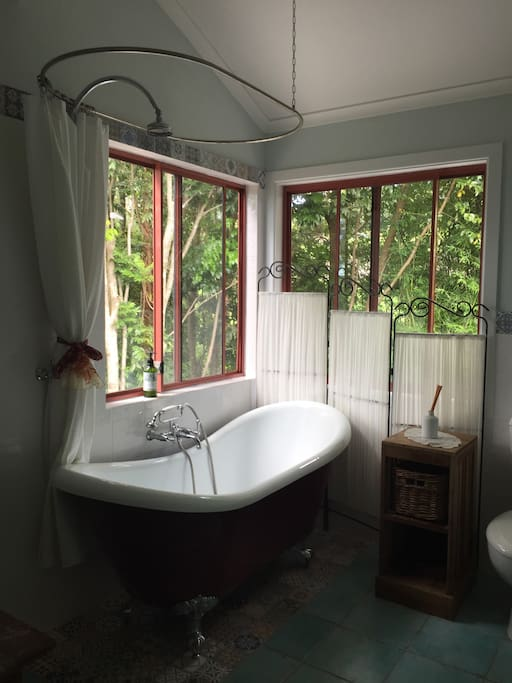 Luxurious claw foot bath with overhead shower, looks out on to rainforest, beautiful any time of day and so relaxing