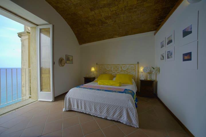Camera da letto matrimoniale vista mare ,bagno , soffitto a volta in antichi mattoni.Bagno in camera con vasca e affaccio sulla scalinata del cortile