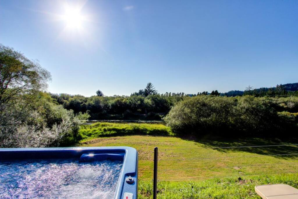 Hot tub looking over grass field (in summer) and channel.