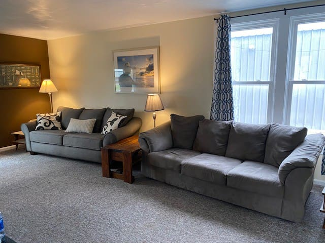 spacious living room with 2 sleeper sofa and large wall mounted smart TV