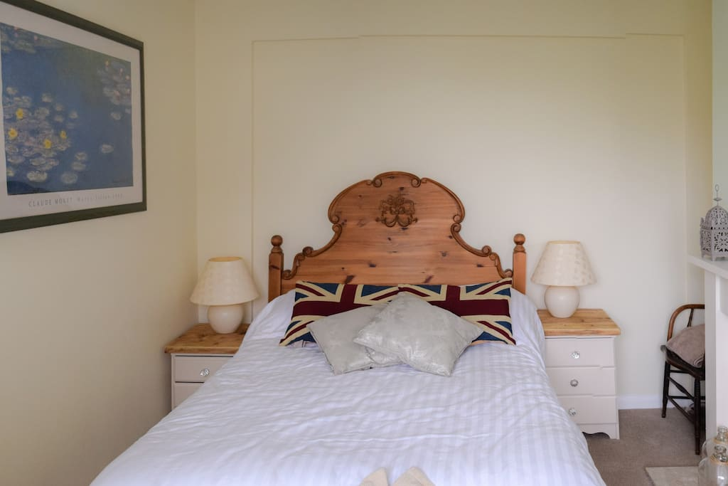 The bedroom faces the front garden and is equipped with a stunning double bed and a small work area.