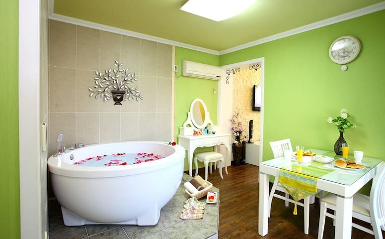 편안한 안정을 주는그린빛 침구와 아기자기한 벽지,월풀을 즐길 수 있는 객실