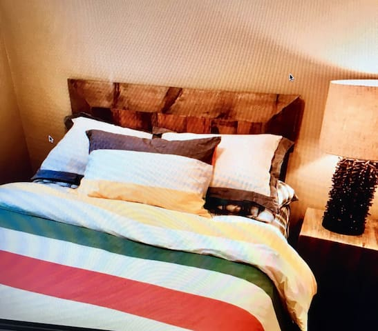 Queen bedroom with cozy HBC linens and custom made barn board headboard.